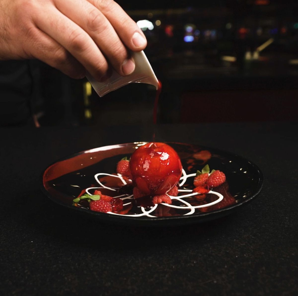 A white chocolate sphere with fresh raspberry