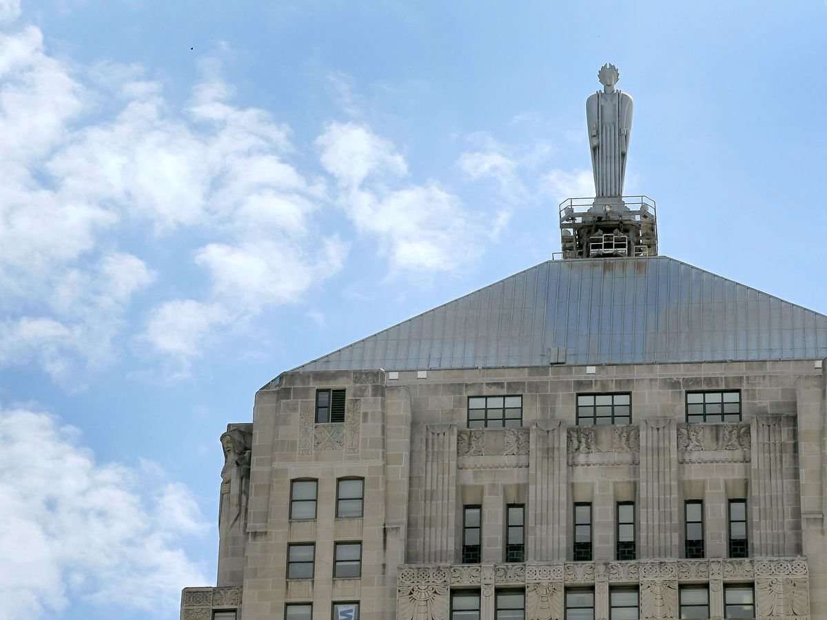 The top of a building in Chicago with a sculpture of a person called Ceres. The sculpture is on top of the building.