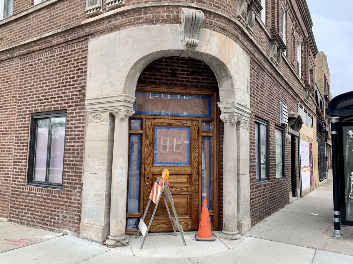 A corner building with a large wooden front door. An orange construction cone and construction barrier sit in front of the door.