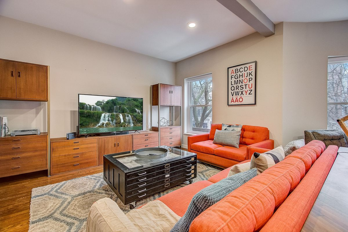 A living room with a large TV, a wood shelving unit, and an orange couch.