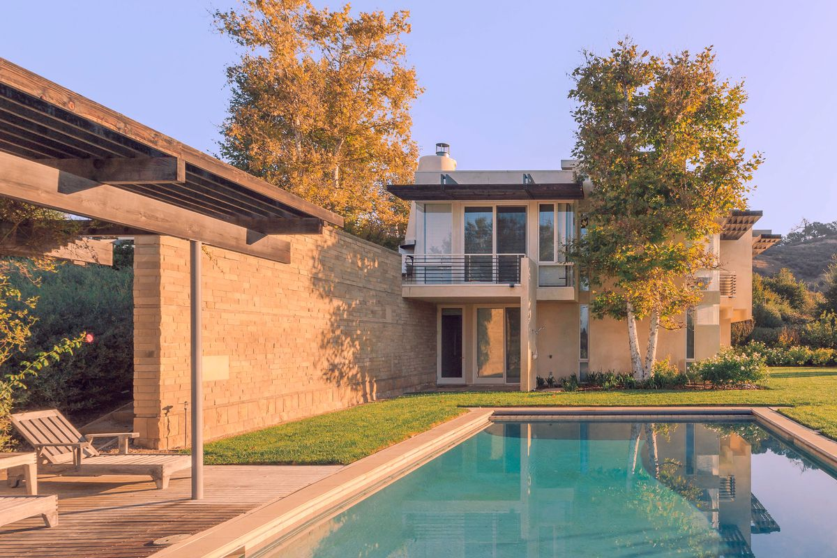 View of modern home from in-ground pool.