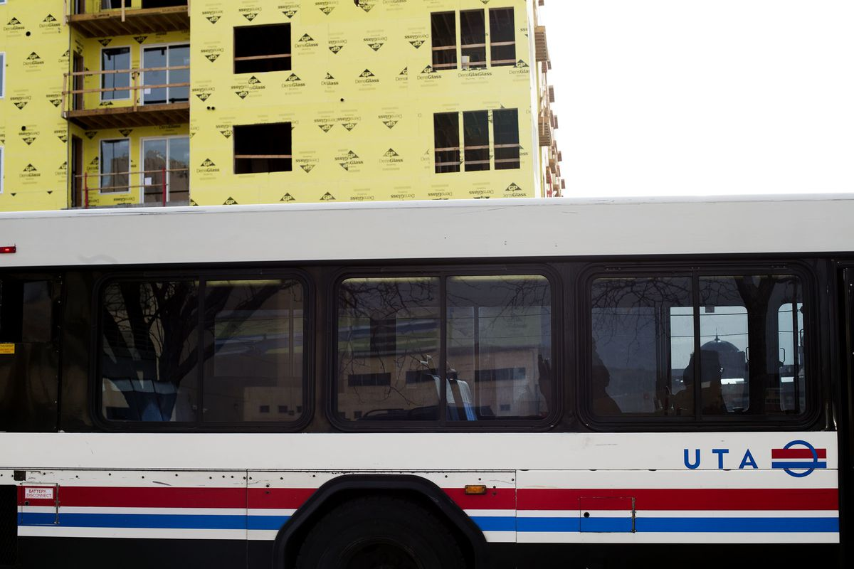 FILE - A UTA bus moves along 200 South while construction of a luxury apartment building progresses in Salt Lake City on Wednesday, Jan. 31, 2018. The sweeping bill from the Legislature's Transportation Governance and Funding Task Force has been scaled ba