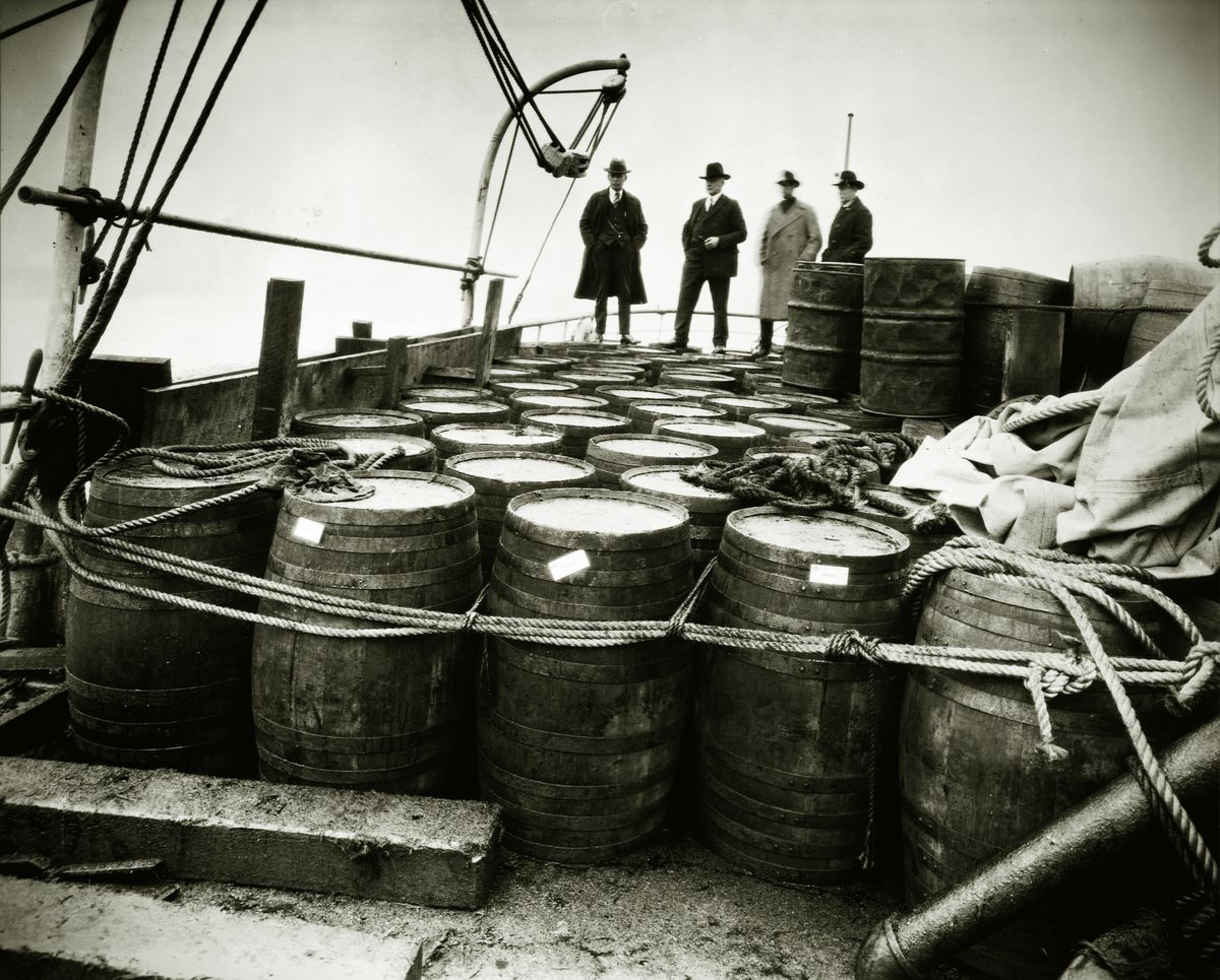 """Prohibition agents aboard the Coast Guard cutter USS Seneca examine barrels of alcohol from a """"rum runner"""" boat."""