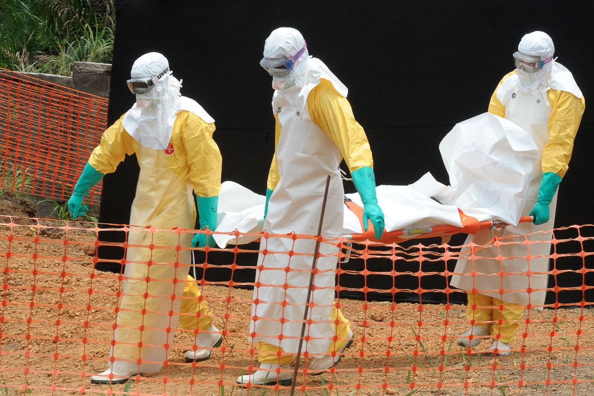 Staff from Doctors Without Borders carry the body of an Ebola victim.