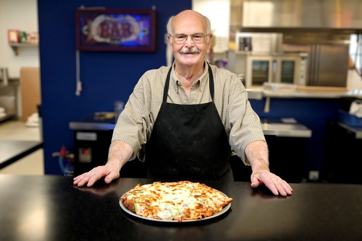 a man in front of a pizza