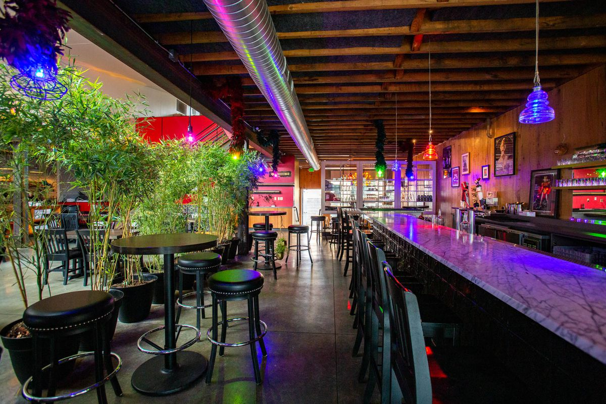 A view of the bar at HoneyHole, illuminated by colored lights and framed to the left by bamboo plants