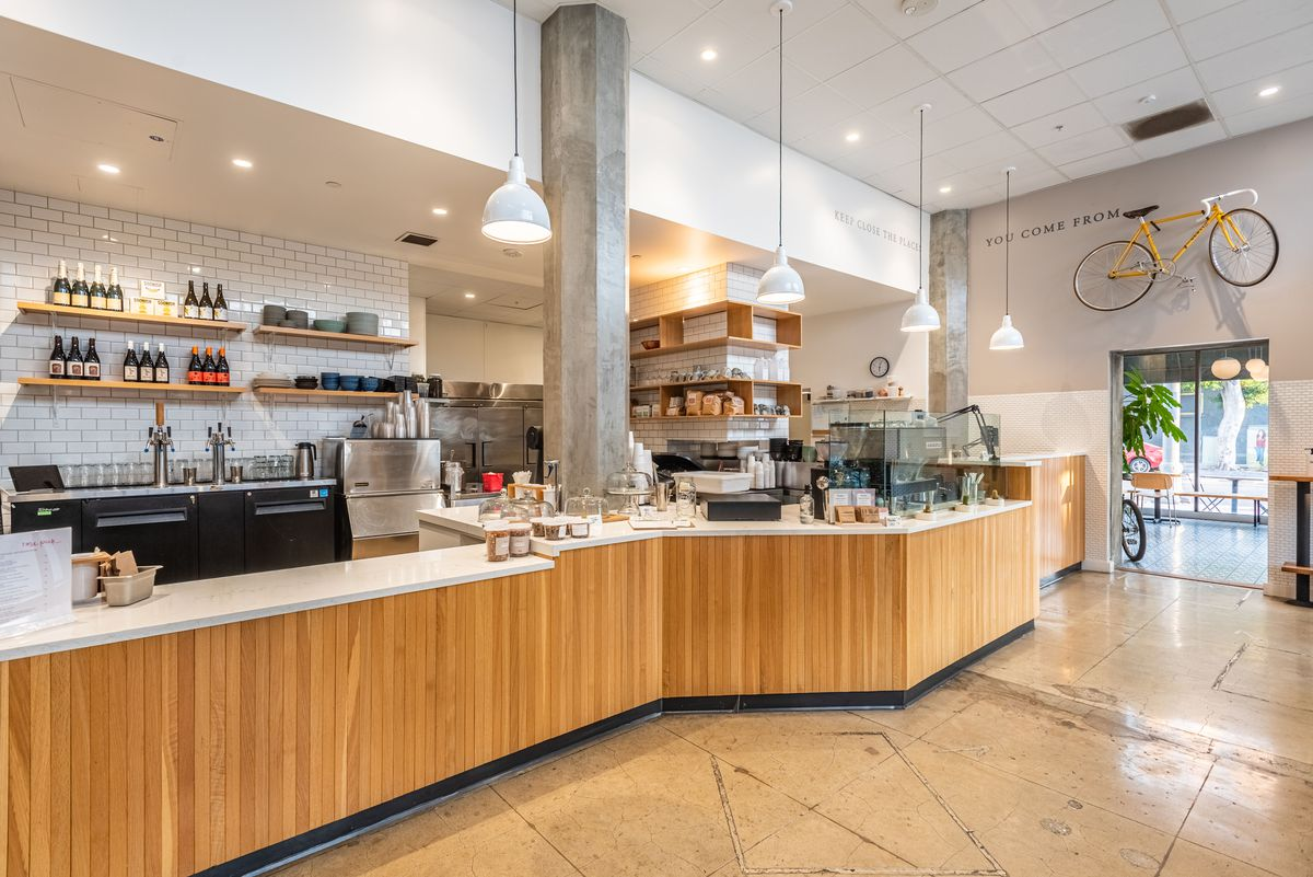 An open plan with cement and tile coffee shop.