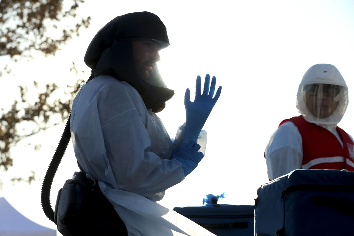 A worker puts on a pair of new gloves at a COVID-19 drive-thru test site at the Maverik Center parking lot in West Valley City on Thursday, Nov. 5, 2020.