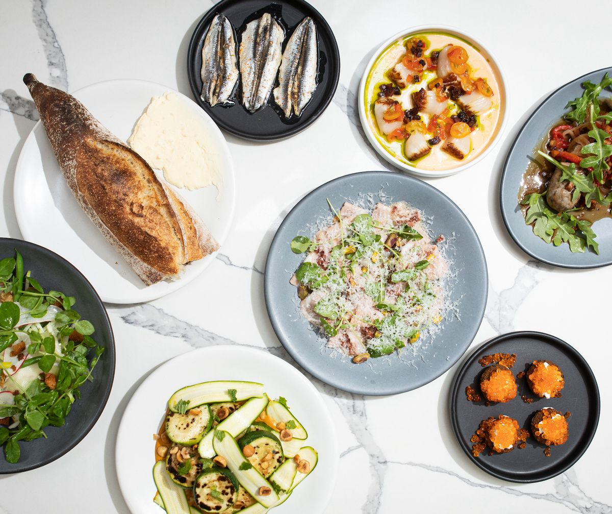 An overhead photograph of an assortment of dishes on a white marble countertop, including baguette, scallop crudo, and multiple salads.