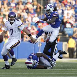 Aug 16, 2013; Orchard Park, NY, USA; Minnesota Vikings quarterback Christian Ponder (7) is chased by Buffalo Bills defensive end Jerry Hughes (55) and cornerback Ron Brooks (33) during the second quarter at Ralph Wilson Stadium.