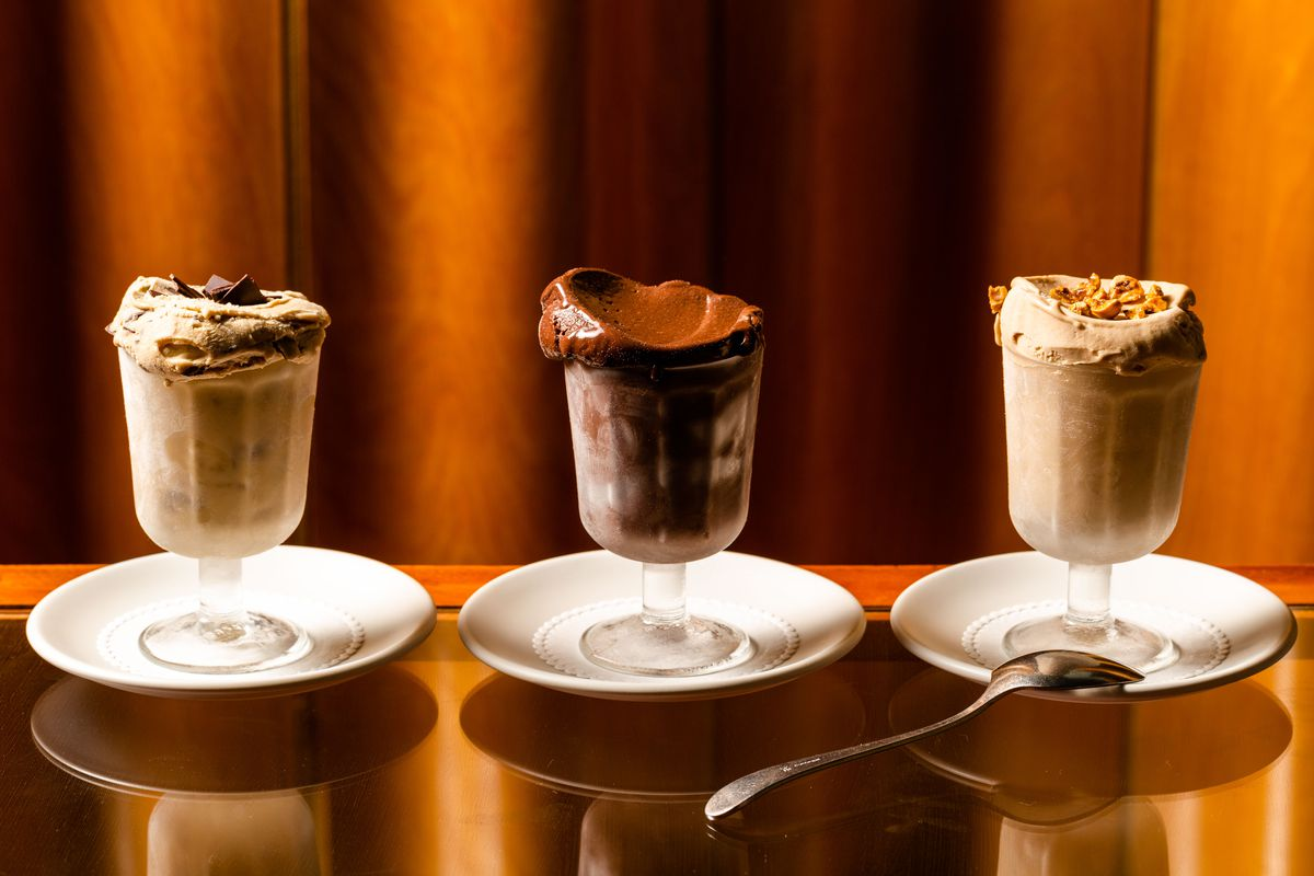 A lineup of three gelatos scooped into stemmed glassware and resting on white saucers.