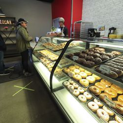Customers pickup donuts at Cowboy Donuts in Spanish Fork on Tuesday, April 14, 2020. Podium has developed and released, free of charge, an interface that allows food businesses to operate takeout services entirely on a text chain from ordering to payment.