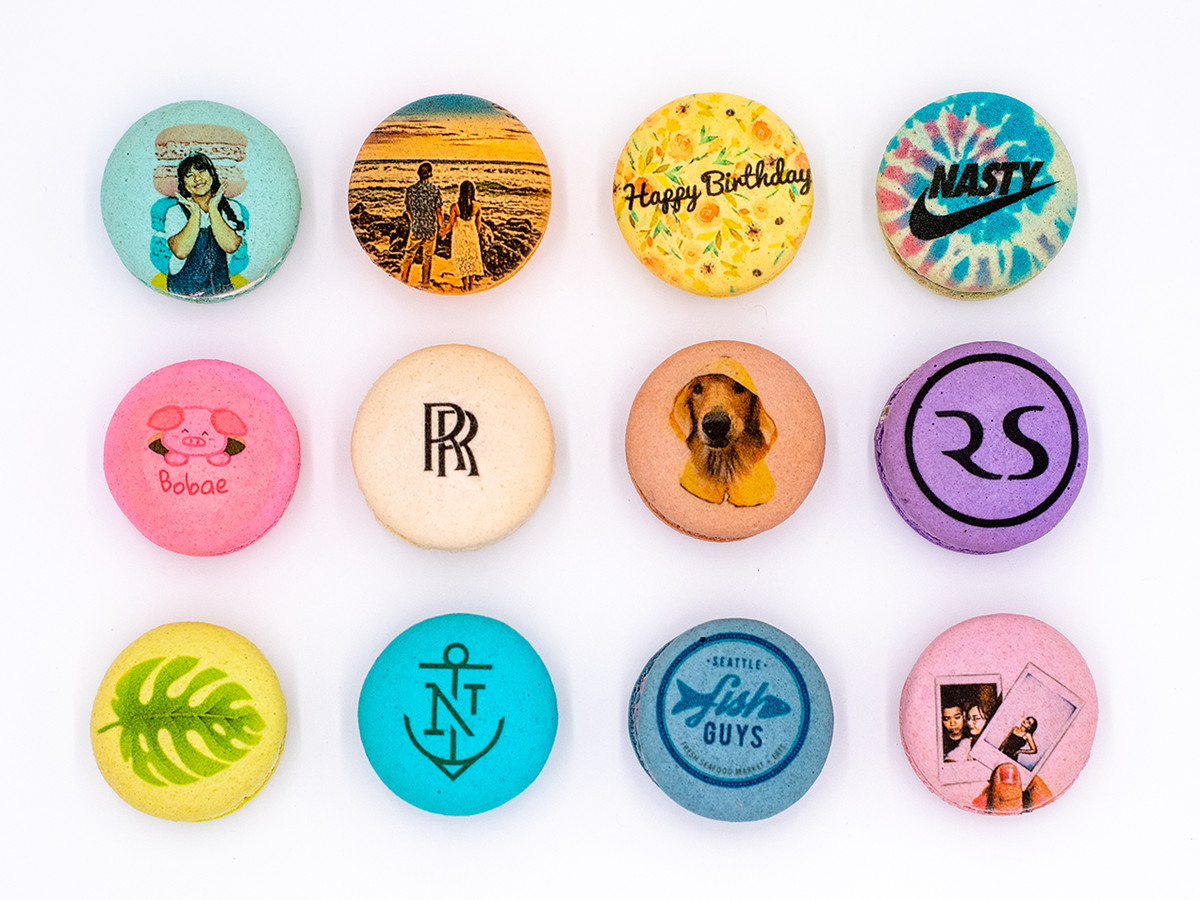 A dozen macarons in a variety of colors, displaying logos, photos, and illustrations on top