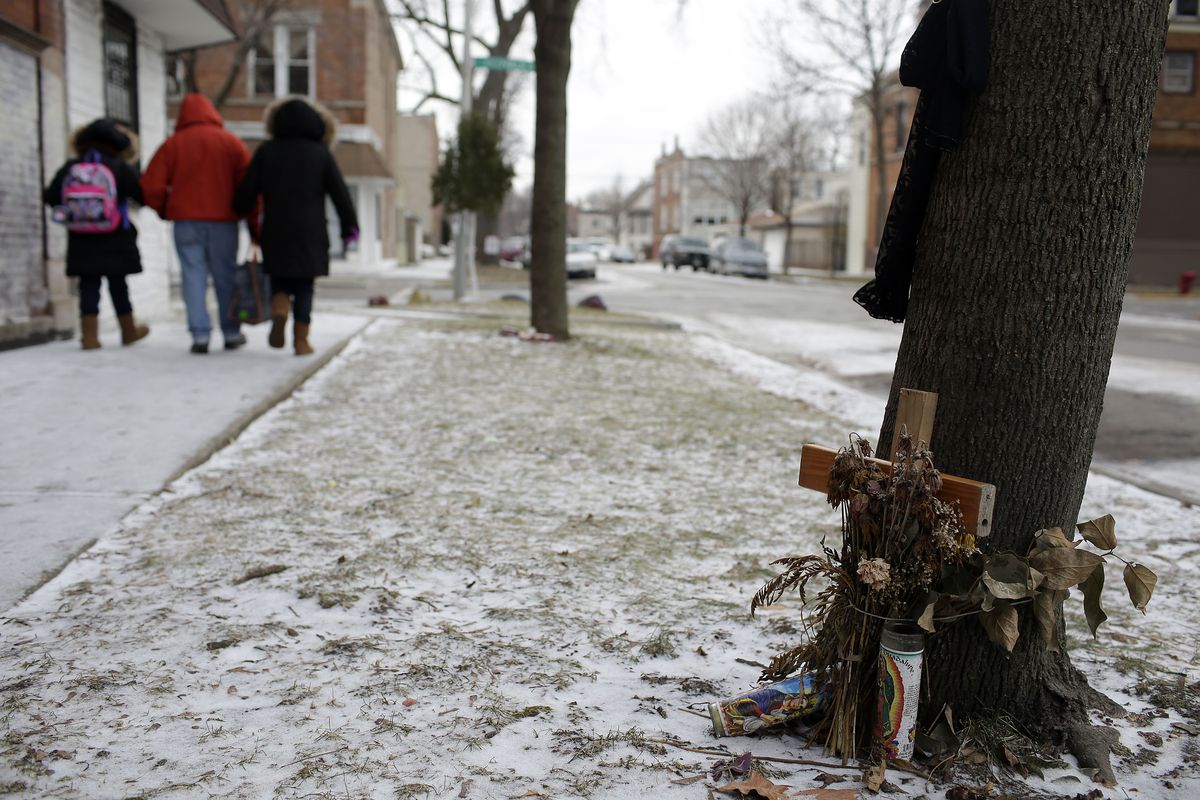 People walk past a makeshift memorial to someone who was killed. | Joshua Lott / The Trace