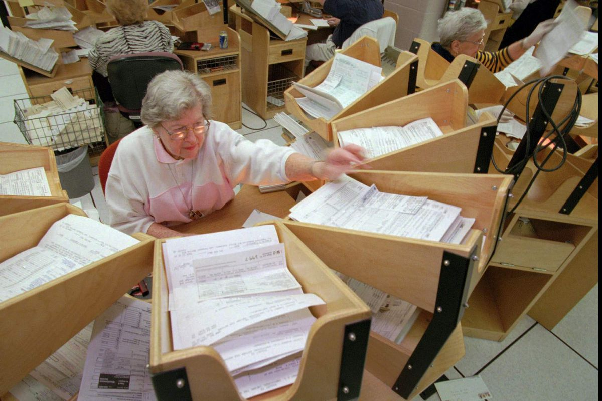 Internal Revenue Service employee Anita Mittelman opens federal income tax returns and sorts them into a tingle table Tuesday, April 14, 1998, at the Philadelphia office.