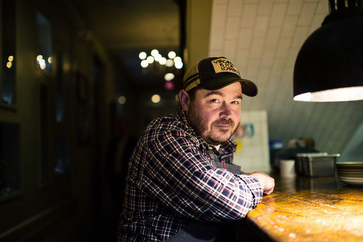 Chef Sean Brock leaning on a counter in a dimly lit room