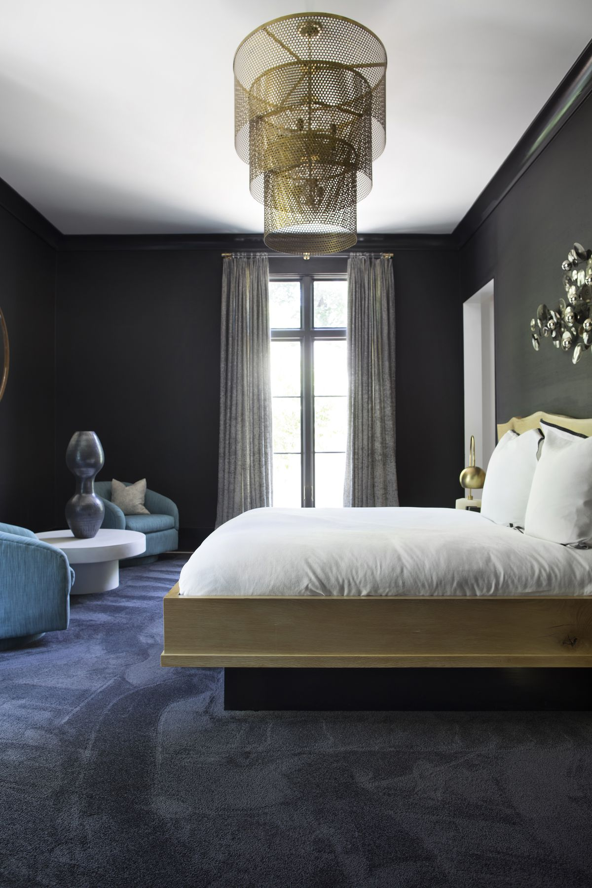 A bedroom has an oversized, tiered, brass-toned light fixture; black grasscloth walls, and a live-edge, natural wood bed.