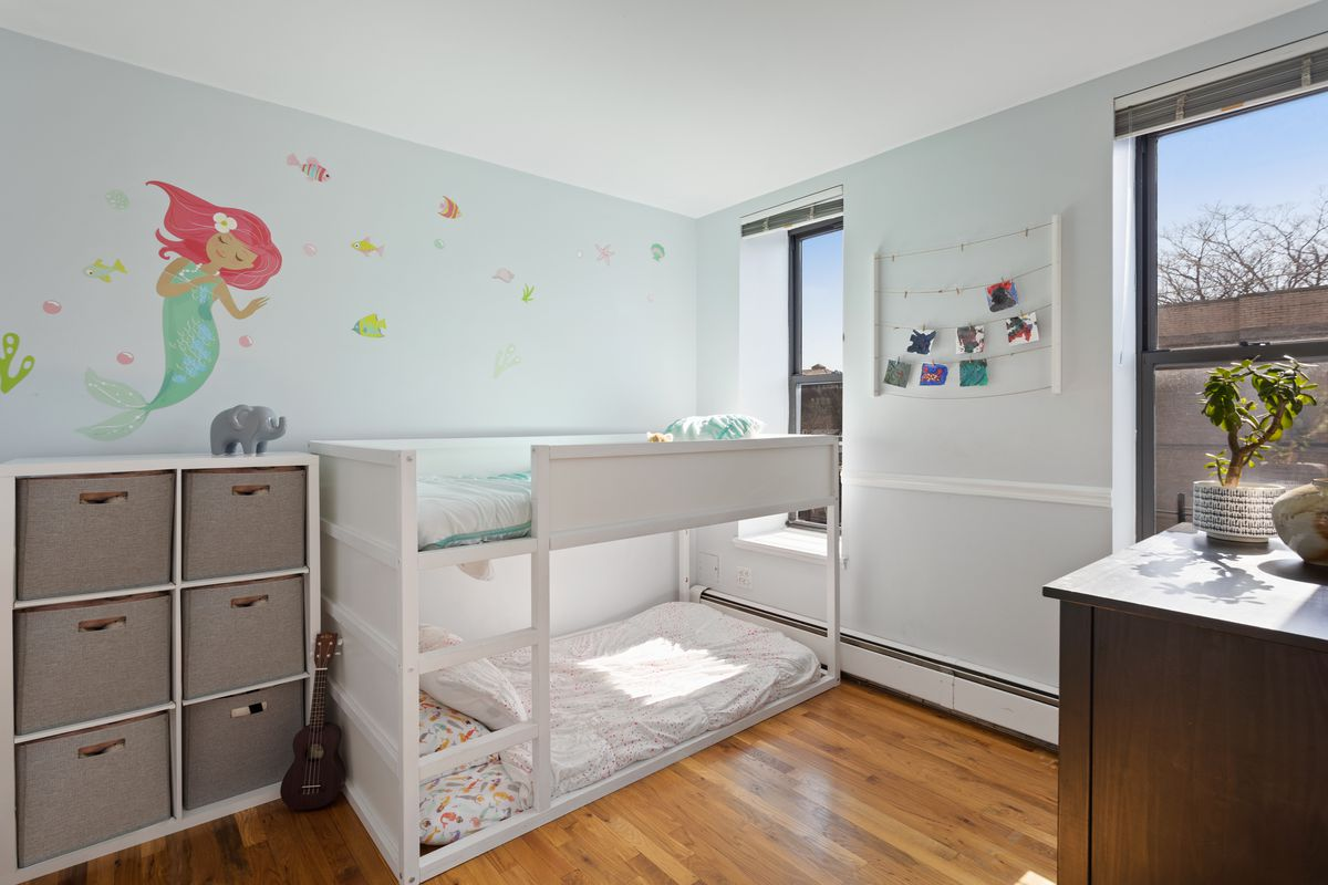 A small bedroom with toddler-sized bunkbeds and two windows.