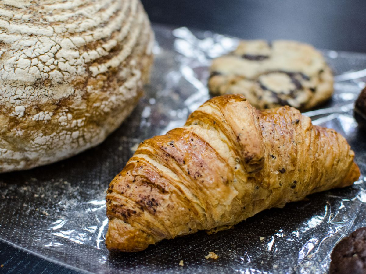 Closeup of a croissant, with a round loaf of bread and several cookies visible in the background. All sit on a piece of plastic on a dark table.
