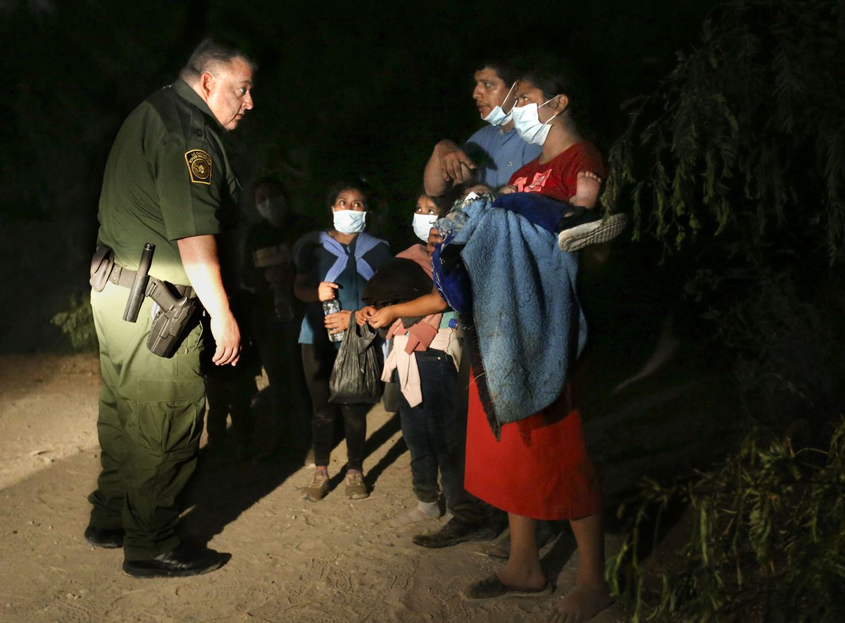 Supervisory Border Patrol agent and Rio Grande Valley sector chaplain Robert Hess questions a group of undocumented migrants from Guatemala and and El Salvador just outside the border wall in McAllen, Texas, on Tuesday, June 22, 2021.