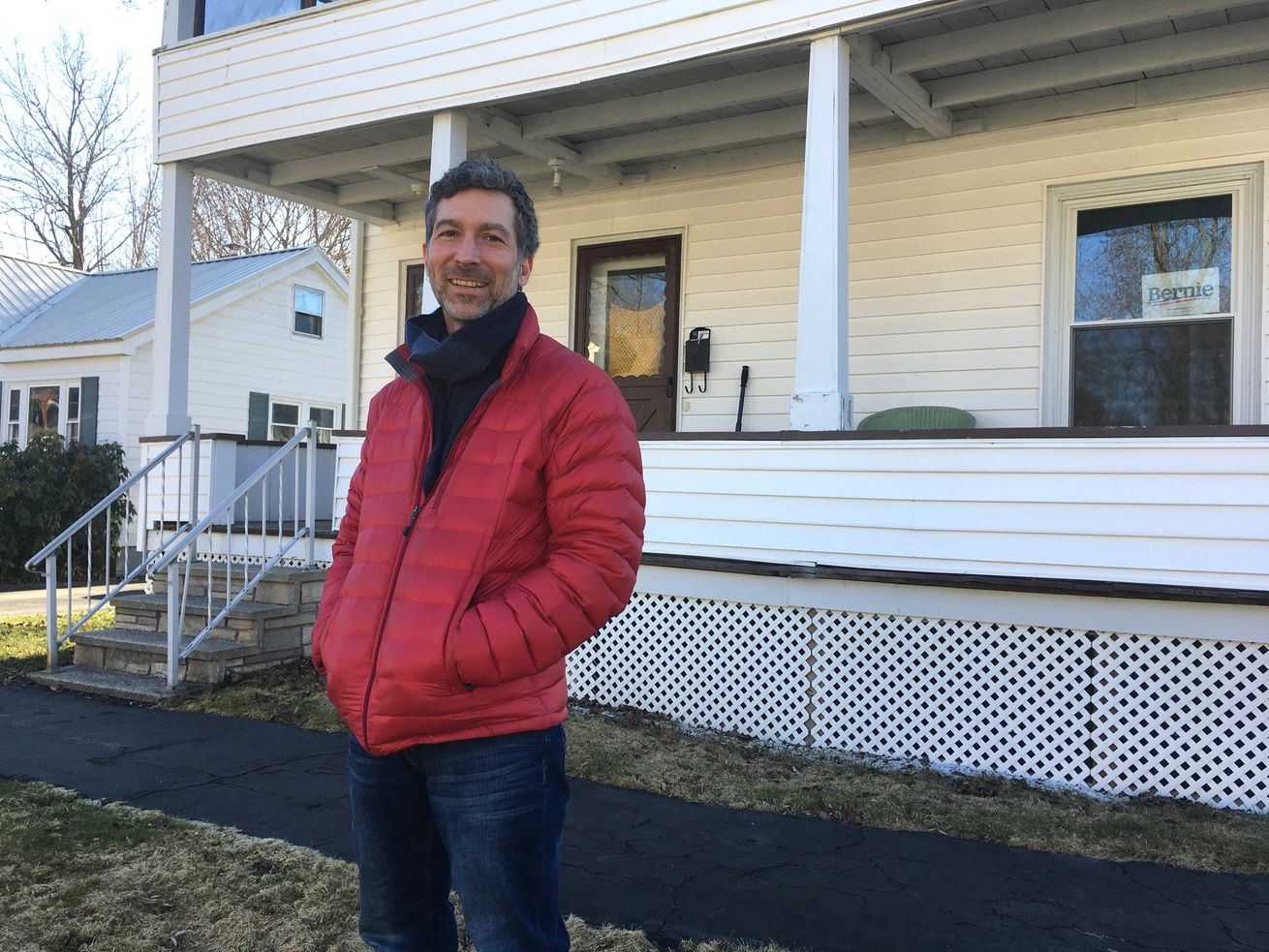 Nichols, in a red puffy jacket and jeans, stands in front of a two-story house on a sunny day.