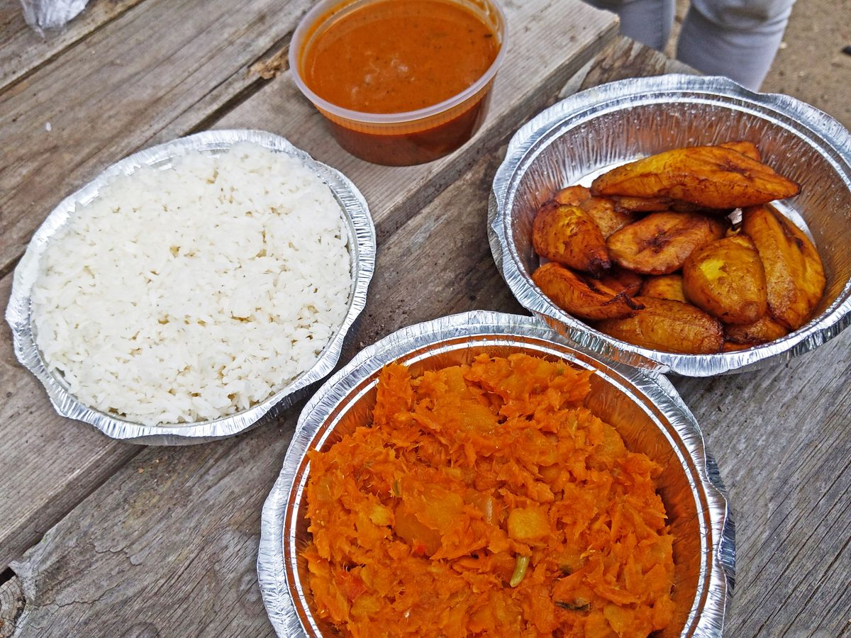 Round tins on a wooden table of red cod casserole, red beans, white rice, and fried sweet plantains.