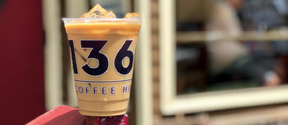 A plastic cup of ice coffee. Part of the cafe's branding is visible on the cup —large numbers 1, 3, and 6 and the word coffee smaller below.