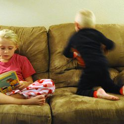 8-year-old Mykenzie Burton reads aloud as 3-year-old Logan rolls around on the couch at home Sept. 25.