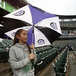 Nine-year-old Katie Stevens, of Denver, uses her umbrella for cover as a light rain envelops Coors Field in Denver before the Colorado Rockies host the Arizona Diamondbacks in a baseball game on Saturday, April 14, 2012. The start of the game had been delayed because of the rainy, blustery weather.