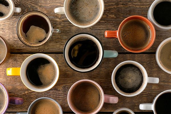 An overhead shot of several coffee mugs with coffee on a wooden table