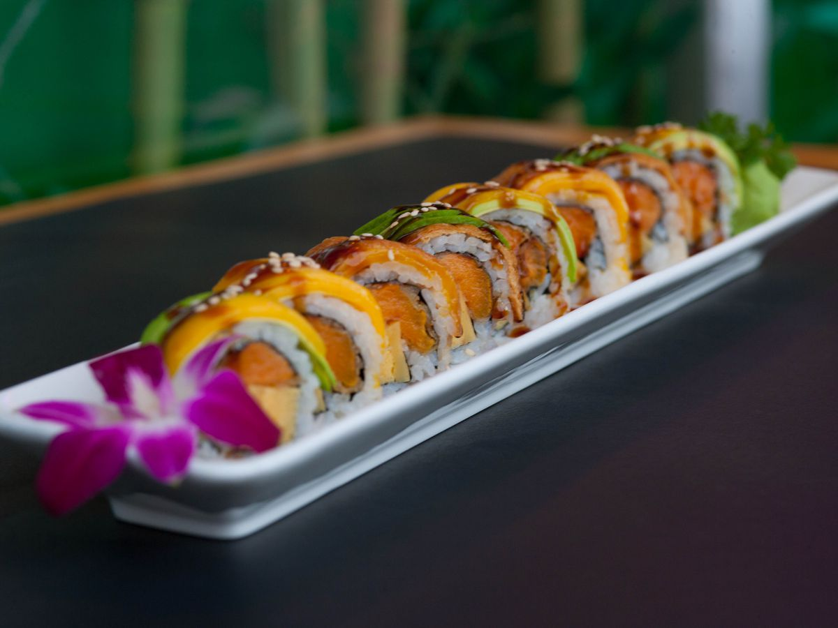 A sushi roll is lined up on a white plate and garnished with an orchid