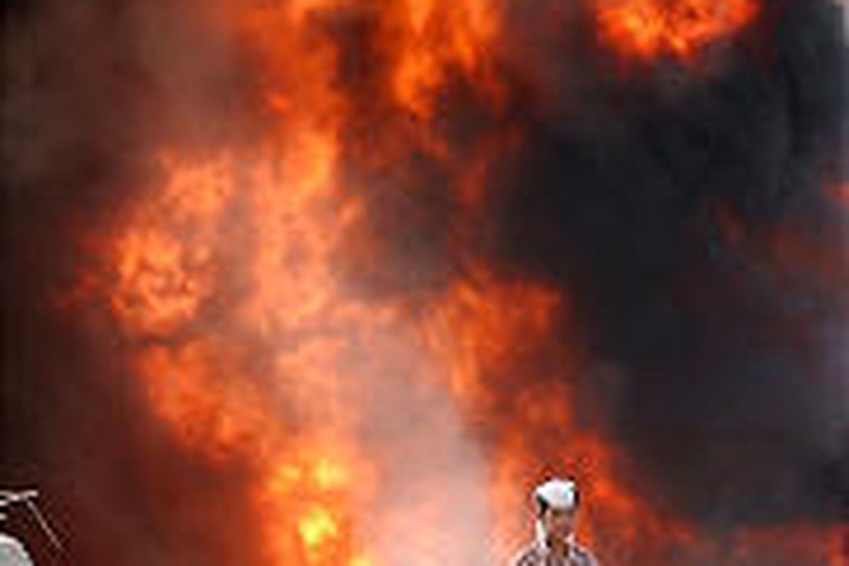 An Iraqi boy walks past a gas pipeline set ablaze by a bomb near Kirkuk on Thursday.