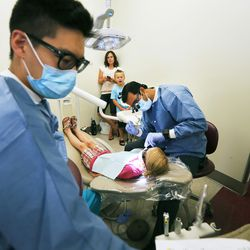 Dental students Kevin Yu and Kiran Napa check out Kenzlie Binks' teeth as Kenzlie's mom, Kim, and brother, Taysen, look on at Roseman University in South Jordan on Tuesday, Aug. 9, 2016. The dental students provided free back-to-school dental exams for children and teens entering grades K-12 during its second annual Back to School Brush-Up event.