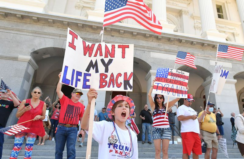 """A group of protesters on the steps of a building hold signs that read, """"I want my life back,"""" and, """"I prefer dangerous freedom to peaceful tyranny."""""""