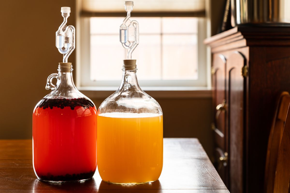 Two big glass jugs contain golden mead and pink mead.