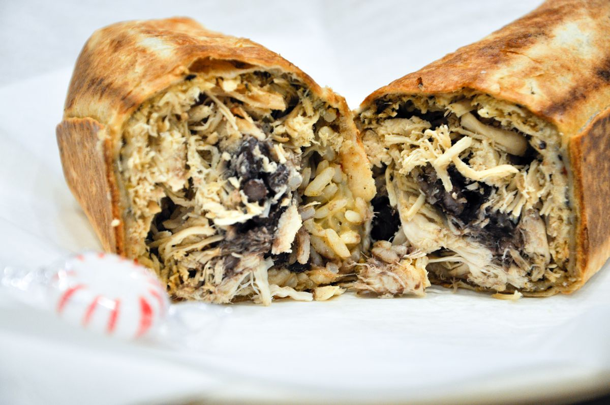Cross-section of a stuffed chicken burrito. A wrapped starlight mint is on the side of the plate.