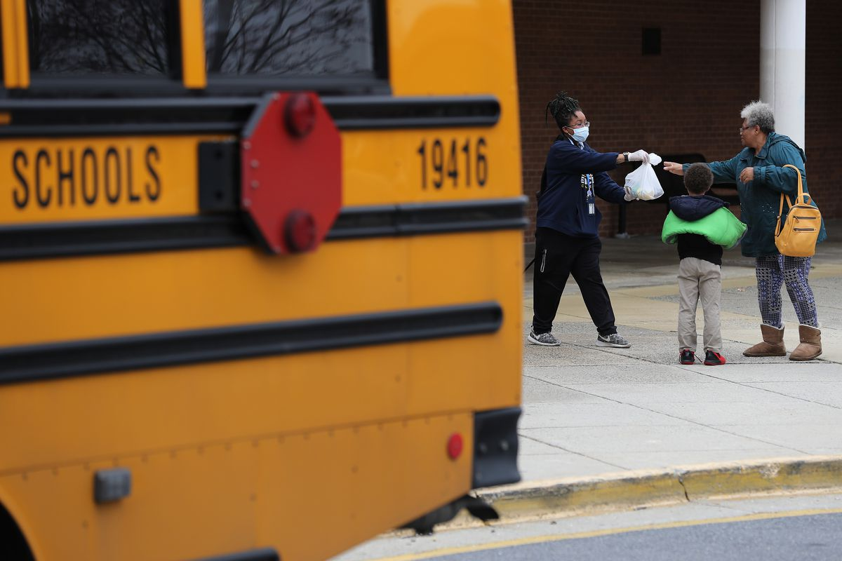 GAITHERSBURG, MARYLAND - MARCH 20: Montgomery County Public Schools Special Needs Bus Attendant Zanashia Rowe helps distribute bags of food donated by Manna Food Center at Quince Orchard High School as part of a program to feed children while schools are closed due to the coronavirus March 20, 2020 in Gaithersburg, Maryland. Millions of children across the country rely on meals they get at school, which are closed in an attempt to suppress transmission of the COVID-19 virus.
