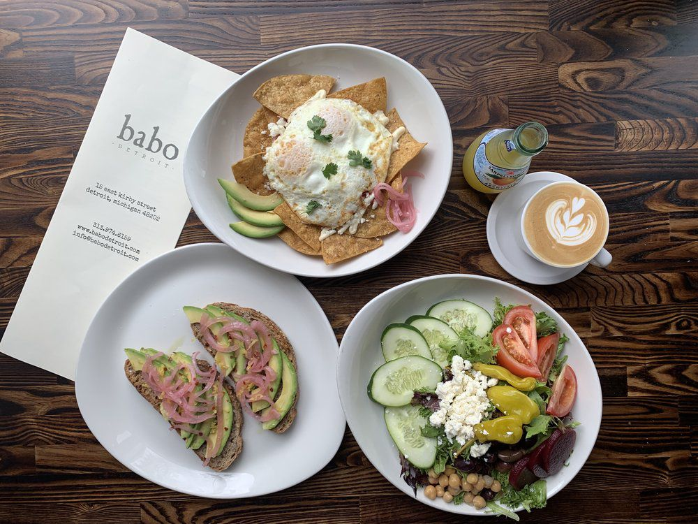 a greek salad, two pieces of avocado toast, chilaquiles, an orangina, and a latte on white china with a babo menu next to it.