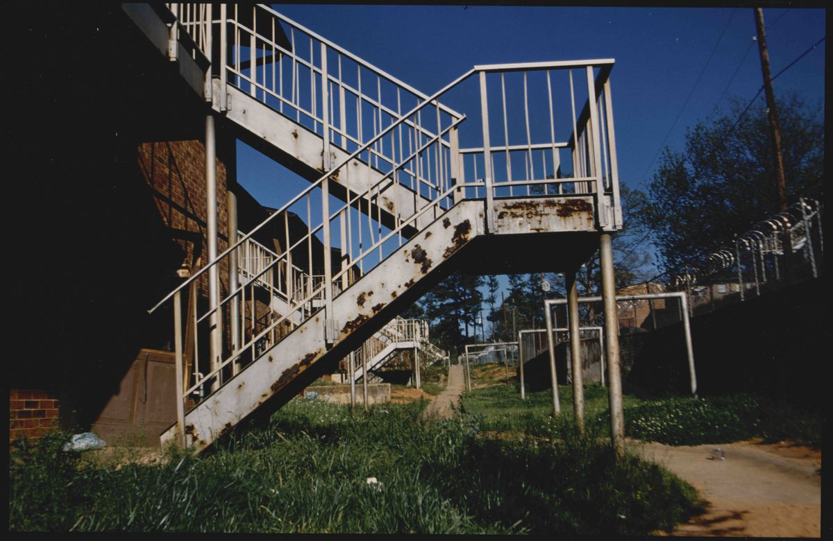 Rusted white apartment stairs with high grass and large section of dry dirt close to the barbwire fence. Square metal beams in the middleground along with stairs leading to other apartments. Trees and powerlines in the background. East Lake, Atlanta, GA. Feb. 12, 1997.