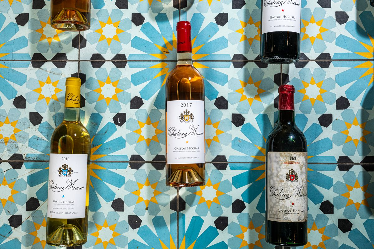 Bottles of white, amber, and red wine from Chateau Musar rest on mosaic tiles with a blue and yellow pattern
