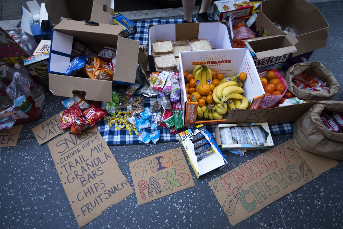 Snacks and cardboard signs photographed on the street before a protest.