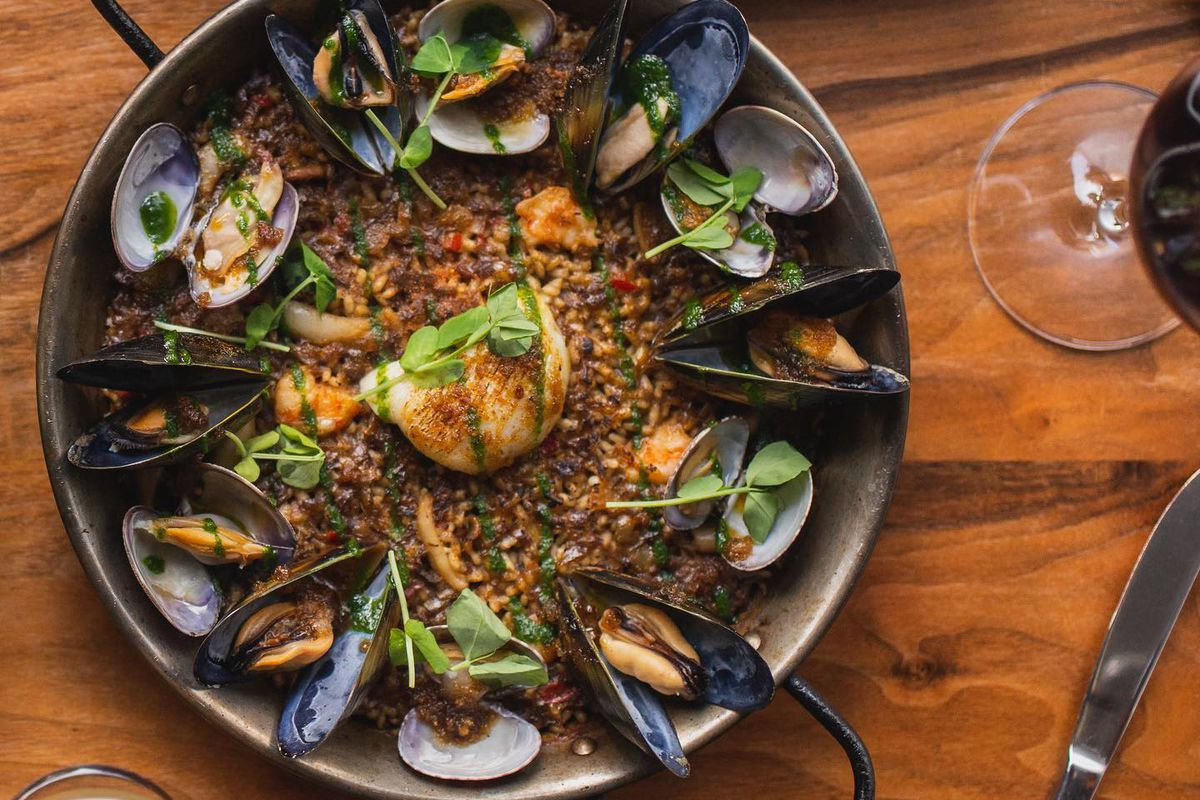 A wooden table bears a paella filled with rice and mussels. A plate with three croquettes sits near it.