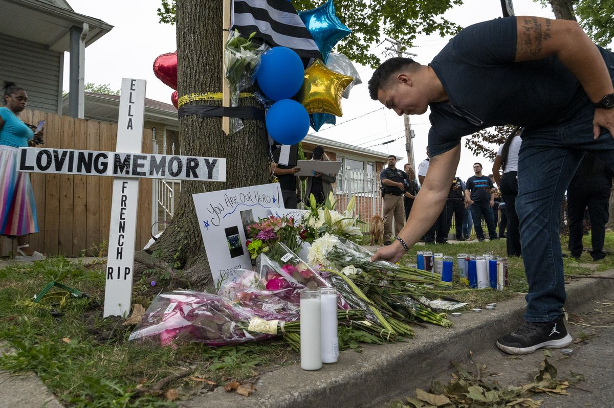 A police officer leaves flowers at the memorial erected to honor Officer Ella French. A vigil was held at the memorial Monday, Aug. 9, 2021.