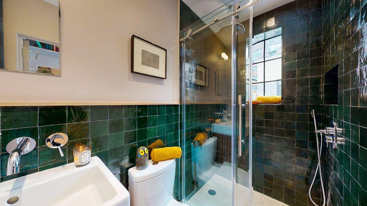 A bathroom with dark green tiles.