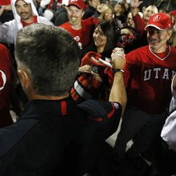Utah Head Coach Kyle Whittingham celebrates with fans after his team destroyed BYU 54-10 Saturday, Sept. 17, 2011
