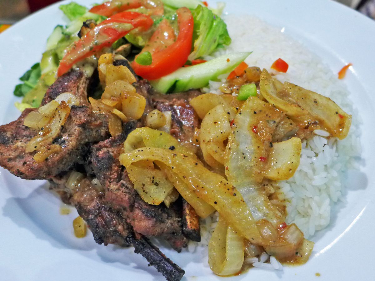 A few charred chops, bones sticking out, smothered in onions with salad and rice.