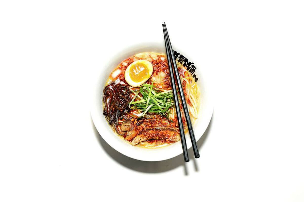 A bowl of ramen, shown from above with soft egg and chopsticks.