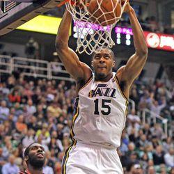 Utah Jazz power forward Derrick Favors (15) dunks on Portland Trail Blazers center J.J. Hickson (21) as the Utah Jazz defeat the Portland Trailblazers 112-102  in NBA basketball Monday, April 1, 2013, in Salt Lake City.