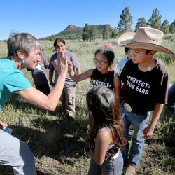 Interior Secretary Sally Jewell gives high-fives to a group of Native American kids near the Bears Ears in southern Utah on Friday, July 15, 2016.