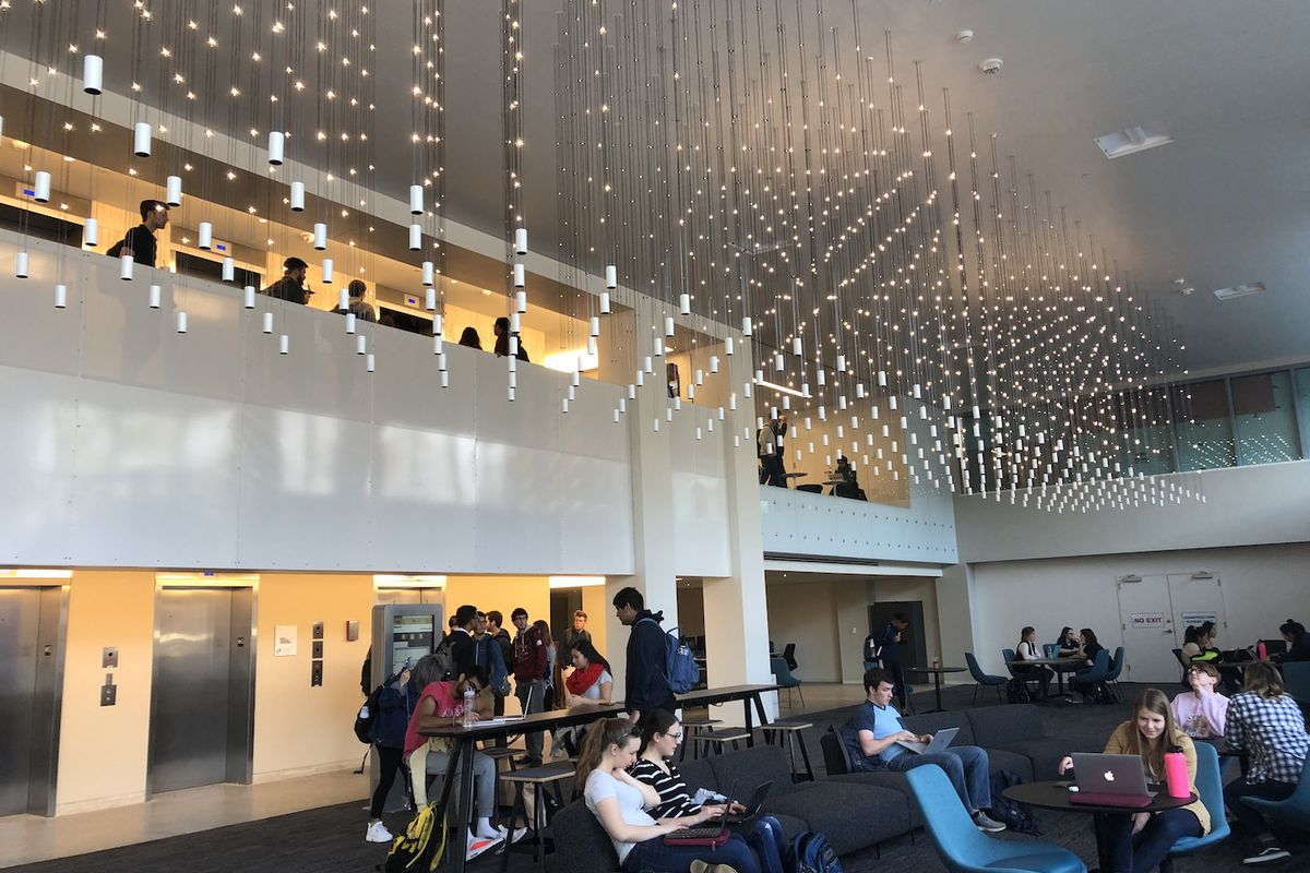 Large atrium with hanging light fixtures and students at tables.